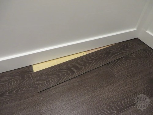 Installing the last corner of laminate flooring without removing baseboards: Start by putting the baseboard end of the flooring under the first baseboard at an angle. Then slide the long edge of the flooring under the other baseboard, straightening the flooring piece into place.