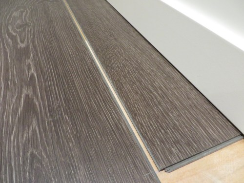 Installing the last row of laminate flooring without removing baseboards: Get those grooves lined up...