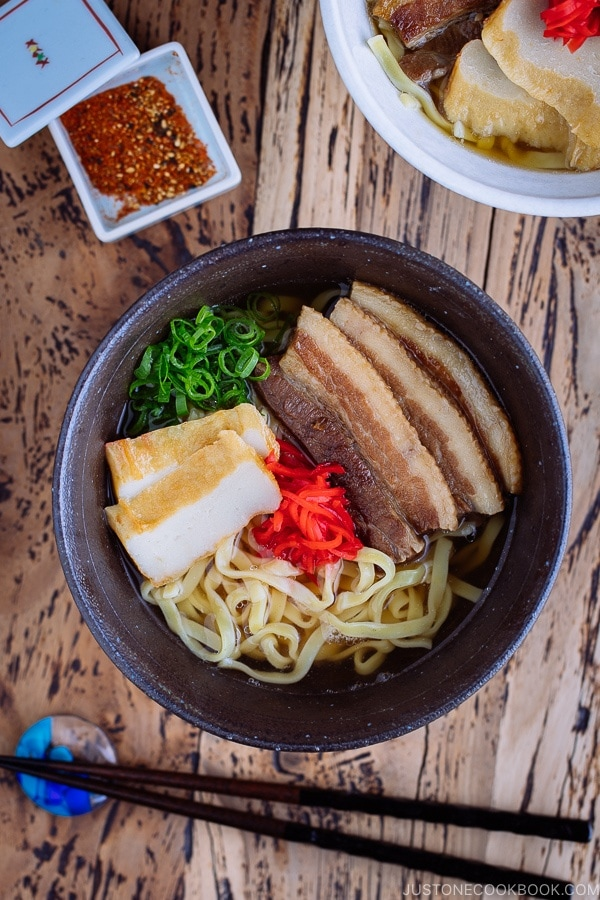 A white bowl containing Okinawa Soba and delicious Japanese dashi and pork broth, topped braised pork belly, fish cakes, green onion, and red pickled ginger.