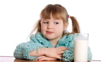 Menina de maria chiquinha, com cabelos lisos, veste blusa azul e olha de lado para copo com leite.