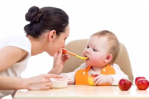 Babá branca de coque dá papinha na boca de neném, sentado em cadeirinha.
