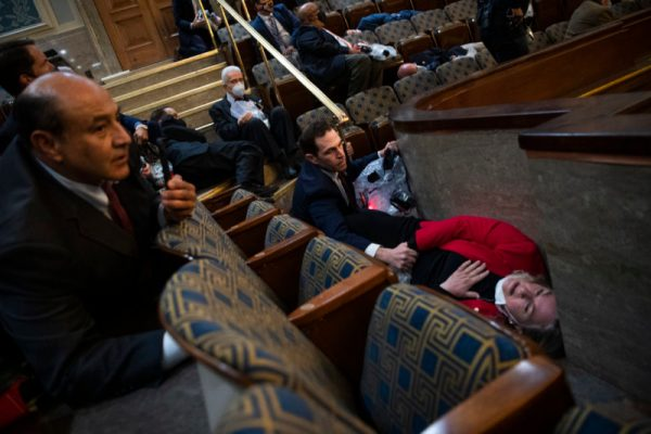 Rep. Jason Crow (D-CO) and Rep. Susan Wild (D-PA) take cover as insurrectionists attack the U.S. on January 6, 2021 during the joint session of Congress to certify the Electoral College vote.