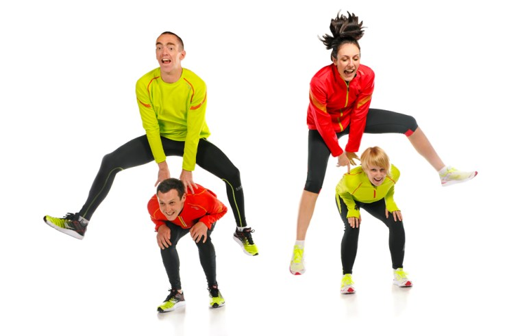 People frog jumping over 2 other people on a white background.