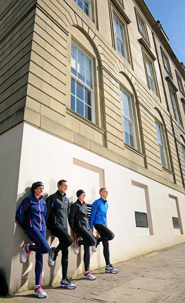 2 males and 2 females leaving against a wall wearing running clothing.