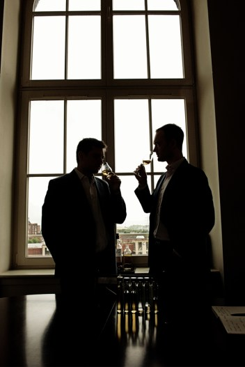 Two mens silhouettes drinking whiskey in front of a large window.
