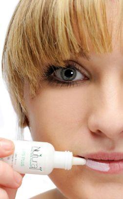 Half a ladies face applying moisturiser to her lips.