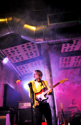 Male guitarist on stage with pink light behind.