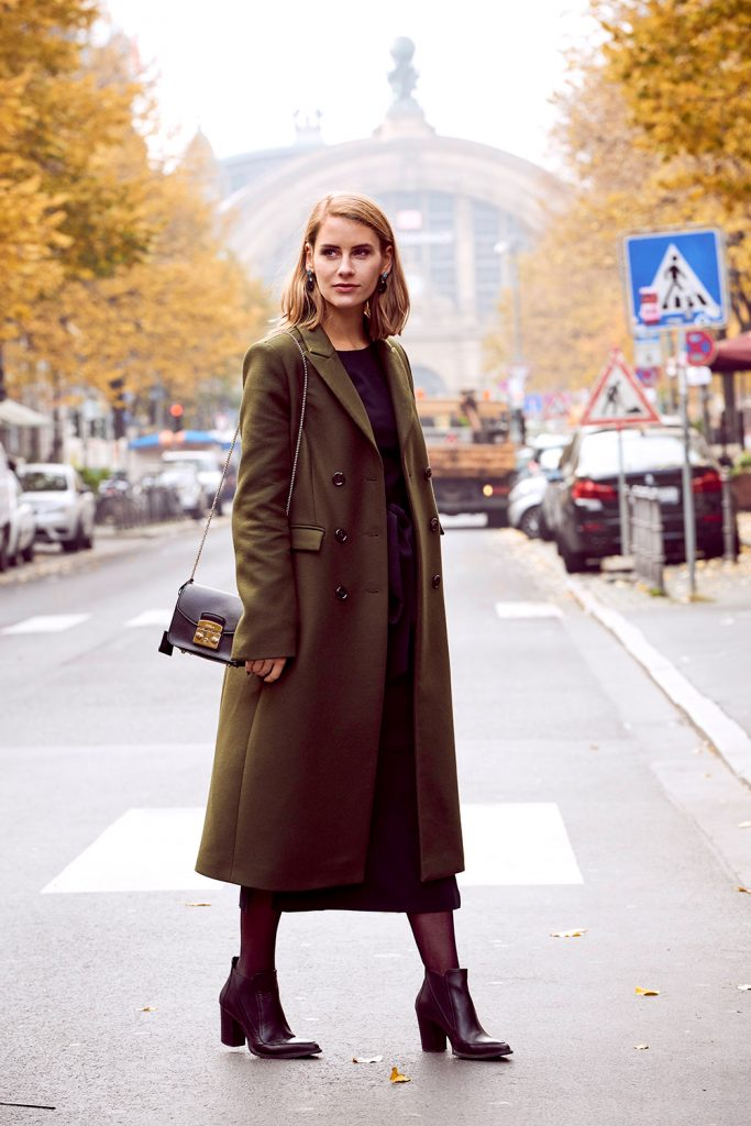 Patricia Exner is classic and sophisticated in a long olive green jacket and belted dress. We love the subtle pop of colour provided by her turquoise earrings. Coat and Dress: Ivy & Oak