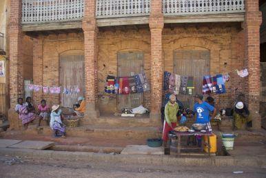 Langs de weg zitten mensen met naaimachines op de stoep te werken.