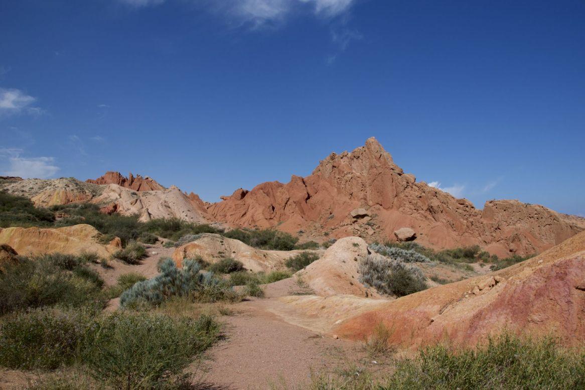 De blauwe lucht steekt prachtig af tegen de gekleurde rotsen.