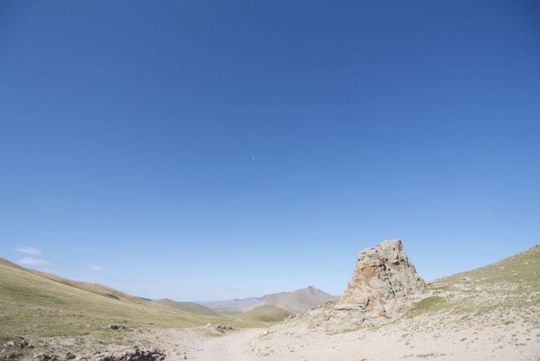 De maan overdag. Hij lijkt erg mini zo hoog boven het uitgestrekte landschap.