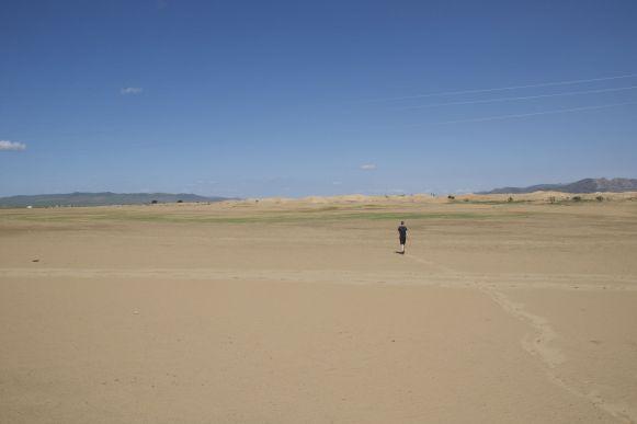 Jur loopt een stukje het zand in om verderop te kijken.
