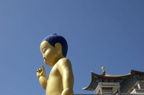 Het goud met blauwe boeddhabeeld kleurt prachtig tegen de strakblauwe lucht.