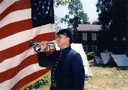 Photo of Jari Villanueva sounding bugle in front of American Flag
