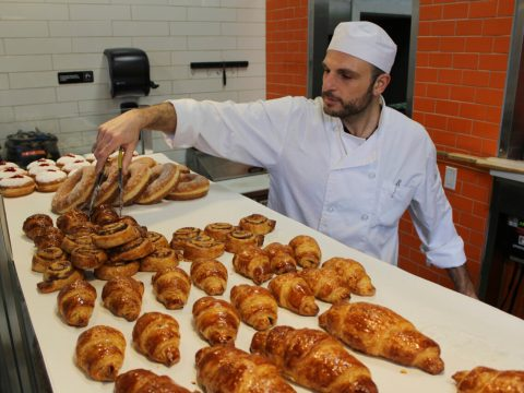 a man in chef's whites looks over a spread of baked goods