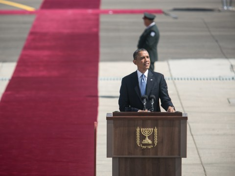 Obama stands at a podium with Israel's menorah seal on it