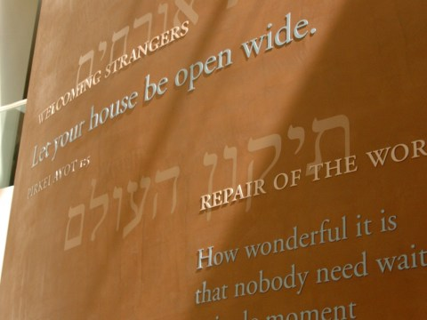 """an inscription on the wall: """"welcoming strangers -- let your house be open wide, pirkei avot"""""""