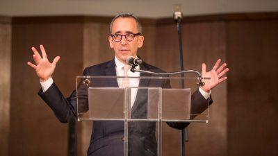 Lezak stands speaking at a podium