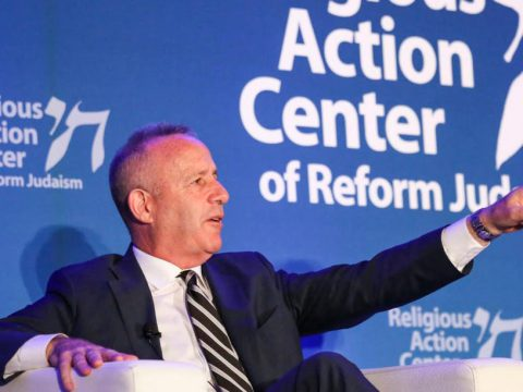 steinberg sits on stage speaking, gesturing with an outstretched arm and index finger
