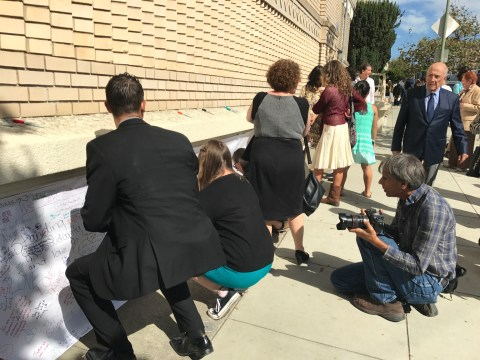 People write positive words on paper covering anti-Semitic graffiti at Temple Sinai in Oakland, Sept. 21, 2017. (Photo/Sue Fishkoff)