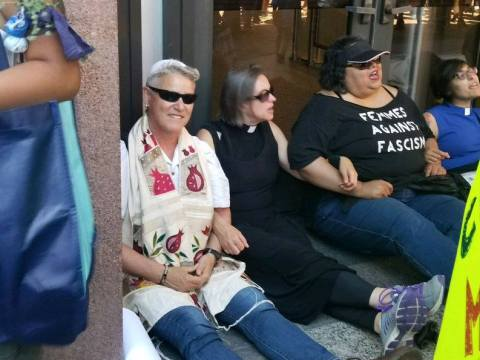 Sue Reinhold of Berkeley (left, wearing tallit and sunglasses) blocks the