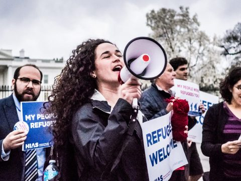 "a woman with a ""refugees welcome"" sign shouts into a megaphone"