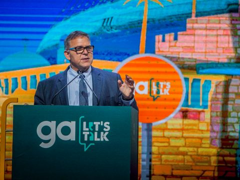 "A man stands at a podium that says ""GA: Let's Talk"" on it"