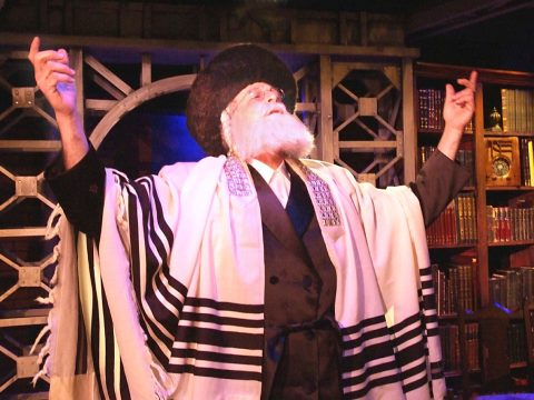 A Hassidic man in a fur streimel hat and tallit, looking up with arms raised in ecstasy