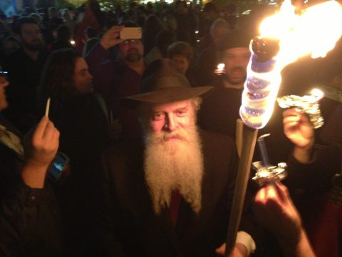 Langer moves through a crowd holding a large torch