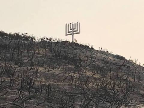 a giant menorah on a hillside stands surrounded by blackened trees and barren ground