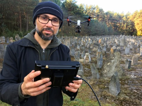 A man in glasses stands with a large remote control device in a graveyard, with a drone hovering nearby