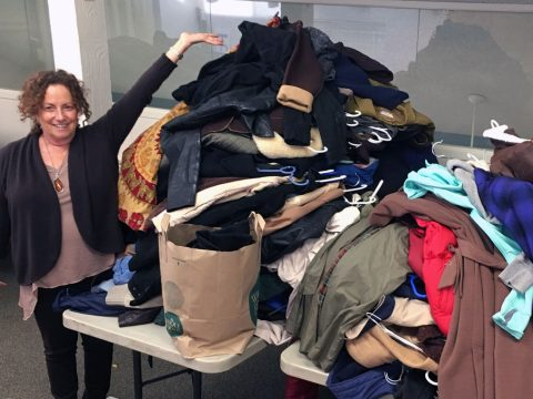 A woman triumphantly gestures at a very large pile of coats