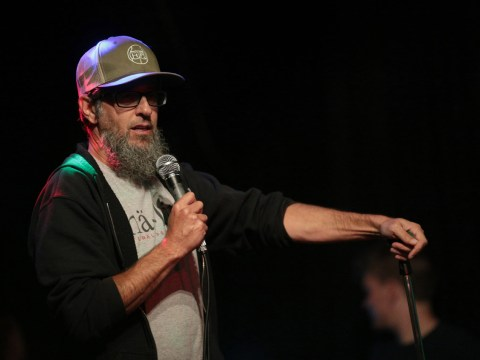 a bearded man in a baseball cap speaks into a microphone