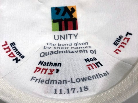 """The special kippot printed for the Friedman-Lowenthal b'nai mitzvah highlights their Hebrew names — the first letters of their names spell out """"unity"""" in Hebrew."""