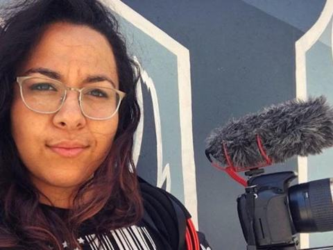 a young woman of color with glasses and windswept hair holding a video camera