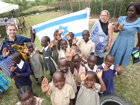 a white man and a white woman stand holding up an Israeli flag with a group of young waving Kenyan children