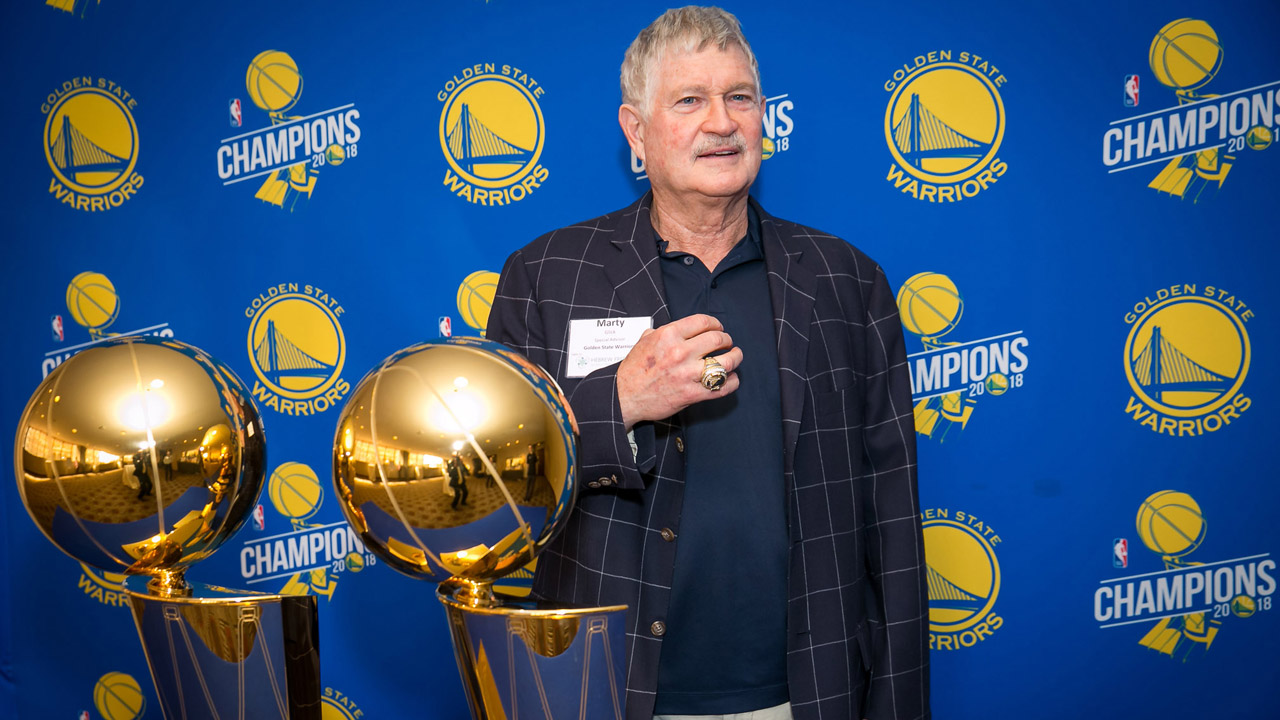 an older an with a mustache stands next to two large basketball trophies