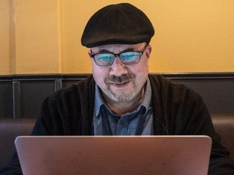 a middle-aged man with a goatee and glasses sets at a laptop, his face illuminated by its screen