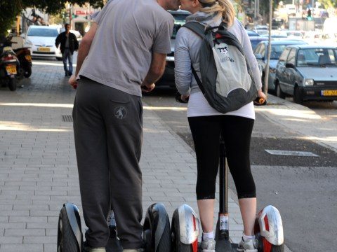 A kissing couple riding their Segway personal transporters around TelAviv.