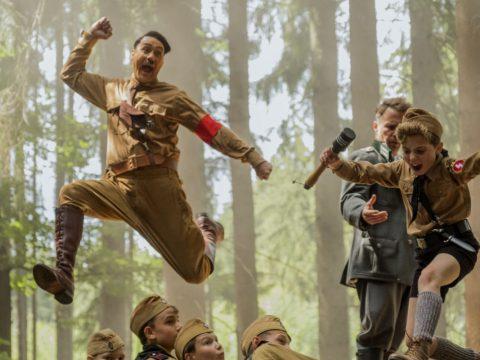 "Taika Waititi, center, wrote and directed ""Jojo Rabbit."" Roman Griffin Davis, jumping to his right, co-stars. (Photo/Kimberley French-Twentieth Century Fox)"