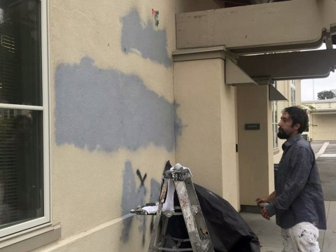 A Burlingame High School staff worker covering up anti-Semitic, homophobic and racist graffiti found on an exterior wall of the school on Sept. 5, 2019. (Photo/The Burlingame B)