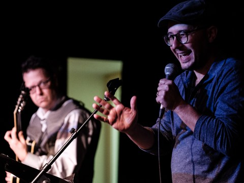 Poet Jake Marmer (right) recites his poetry at LABA's DRUNK event at the East Bay JCC in Berkeley, Nov. 23, 2019, accompanied by guitarist John Schott. (Pete Rosos)