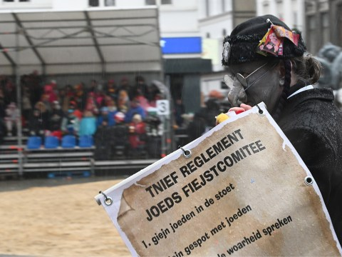 """A man wearing a fake hooked nose and carrying a sign warning readers not to """"tell the the truth about the Jew"""" at the annual procession of the carnival in Aalst, Belgium, Feb. 23, 2020. (JTA/Cnaan Liphshiz)"""