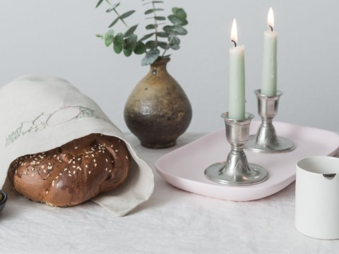 "Nourish Co. Shabbat table items: challah cover with the biblical ""Seven Species,"" a tray for Shabbat candles that color of cherry blossoms and a kiddush cup inspired by the Japanese kintsugi style. (Nicole Morrison Photography)"
