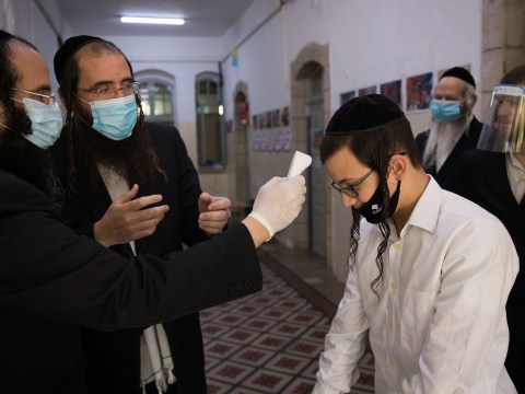 A teacher checks the temperature of a student at a haredi Orthodox school in Jerusalem, May 6, 2020. (Photo/JTA-Nati Shohat-Flash90)