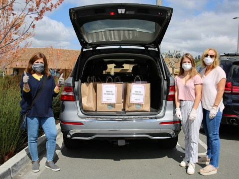 three women in face masks stand at the back a minivan with its back door open and bags of food inside. the leftmost woman is raising her hands in a triumphant double thumps-up.