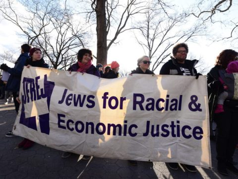 """five people walk with a banner that reads """"Jews for Racial and Economic Justice"""""""