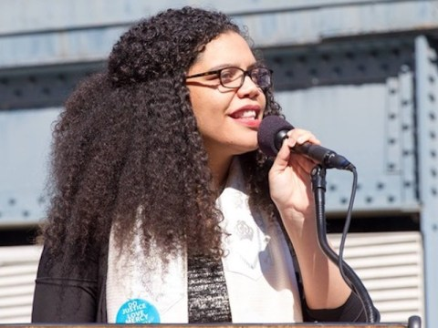 a black woman wearing a talit speaks into a microphone