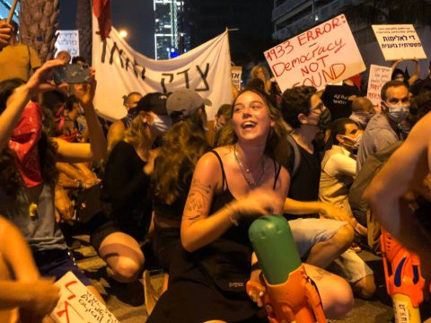 young people sit on the ground block the street, some holding water guns
