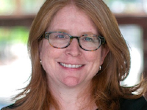 Portait of DDaisy Pellant, the new head of Kehillah School. She is 52, has red hair and glasses.